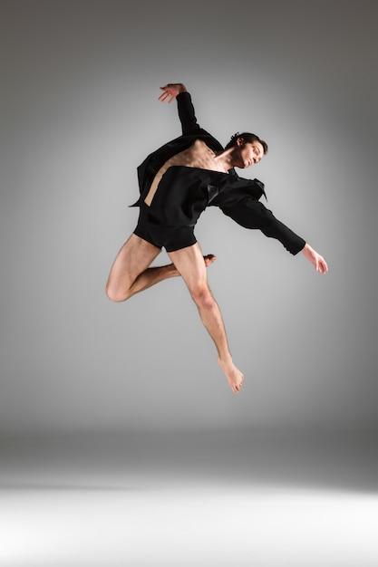 白い背景の上ジャンプ若い魅力的なモダンなバレエダンサー 無料写真