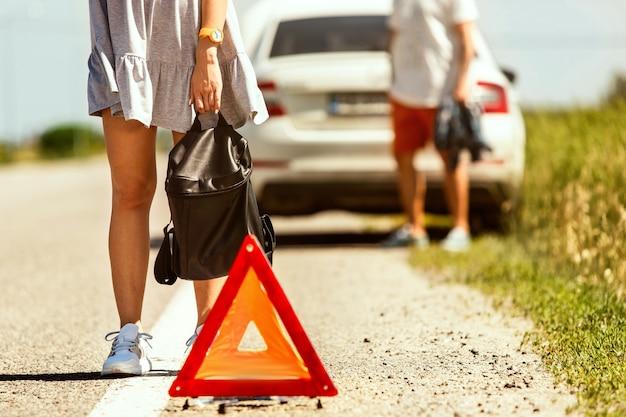 若いカップルは休憩の途中で車を壊した。彼らは他のドライバーを止めて助けやヒッチハイクを求めようとしています。関係、道路上のトラブル、休暇。 無料写真