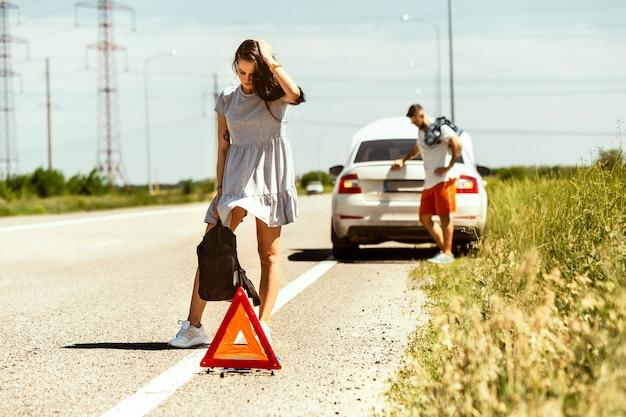 У молодой пары сломалась машина во время поездки на отдых. они пытаются остановить других водителей и просят помощи или автостопа Бесплатные Фотографии