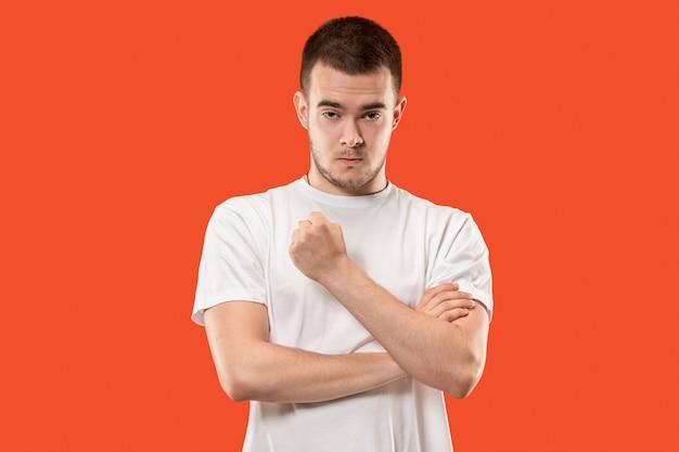 Молодой эмоциональный сердитый человек кричит на оранжевом пространстве Бесплатные Фотографии