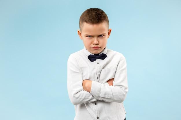 青い空間に若い感情的な怒っている10代の少年 無料写真