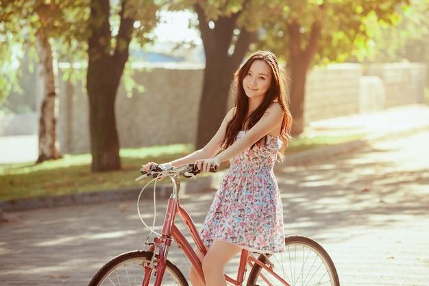 Молодая девушка с велосипедом в парке Бесплатные Фотографии