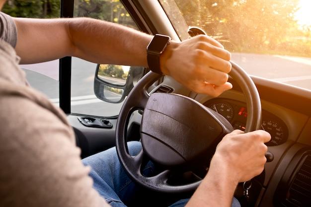 現代の車に座っている彼の手で彼のスマートウォッチを探している若い男 Premium写真