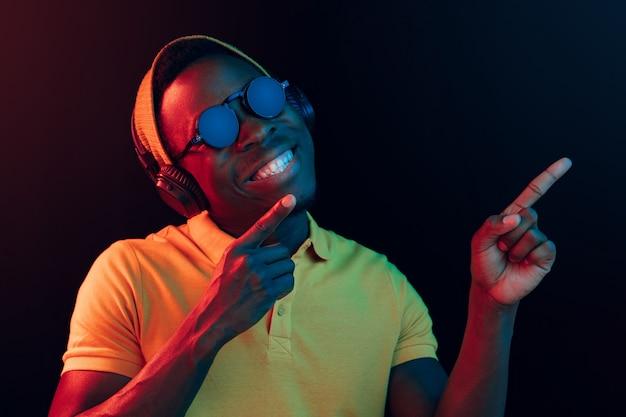 Молодой красивый счастливый битник человек слушает музыку с наушниками в черной студии с неоновыми огнями. дискотека, ночной клуб, стиль хип-хоп, положительные эмоции, выражение лица, танцевальная концепция Бесплатные Фотографии