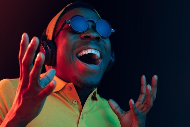 Молодой красивый счастливый хипстерский мужчина слушает музыку в наушниках в черном с неоновыми огнями Бесплатные Фотографии