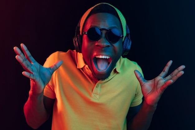 Молодой красивый счастливый удивленный хипстер слушает музыку в наушниках в черной студии с неоновыми огнями. Бесплатные Фотографии