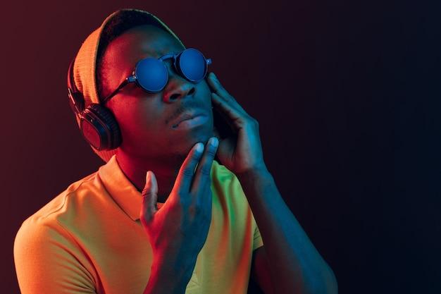 ネオンライト付きの黒いスタジオでヘッドフォンで音楽を聴いている若いハンサムな深刻な悲しいヒップスターの男。 無料写真