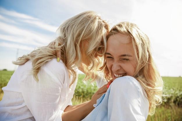 У молодой лесбийской пары сломалась машина, когда она ехала на отдых. поцелуи и объятия на багажнике машины. отношения, неприятности в дороге, отпуск, праздники, концепция медового месяца. Бесплатные Фотографии