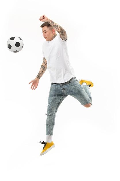 白い背景の上のスタジオでジャンプしてボールを蹴るサッカーサッカー選手としての若い男。 無料写真