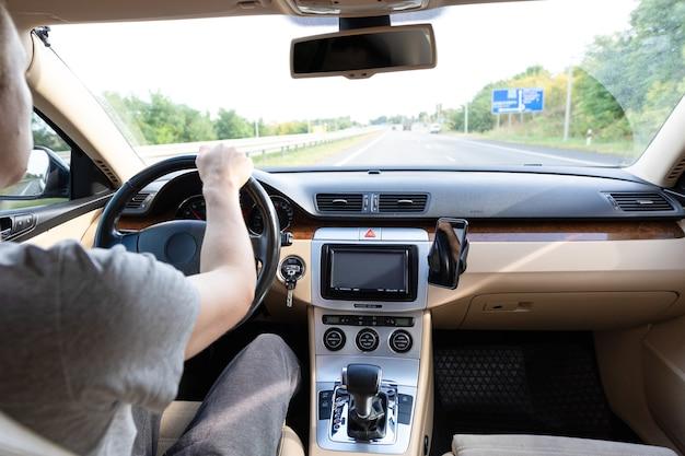 アスファルト道路で現代の車を運転している若い男 Premium写真
