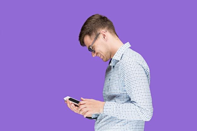 Молодой человек в рубашке работает на ноутбуке в сиреневой студии Бесплатные Фотографии