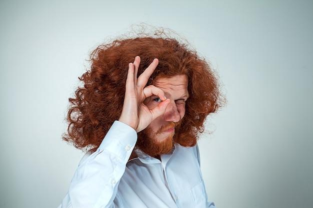 Молодой человек с длинными рыжими волосами смотрит в камеру, прищурившись Бесплатные Фотографии