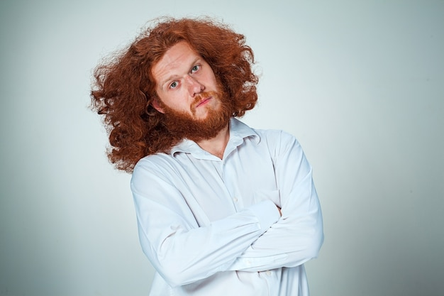 Молодой человек с длинными рыжими волосами смотрит в камеру Бесплатные Фотографии
