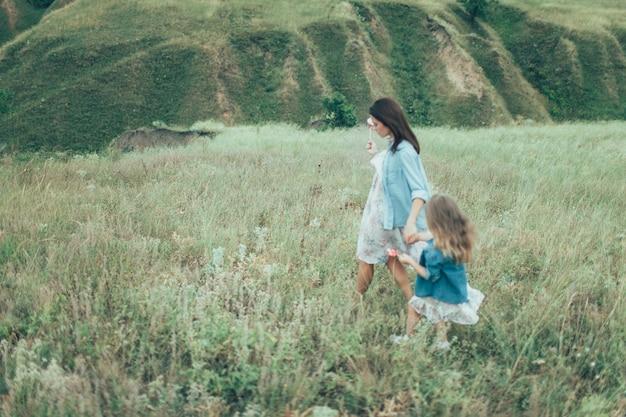 緑の芝生の上の若い母と娘 無料写真