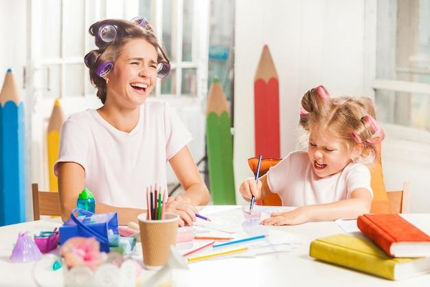 若い母親と自宅で鉛筆で描く彼女の小さな娘 無料写真