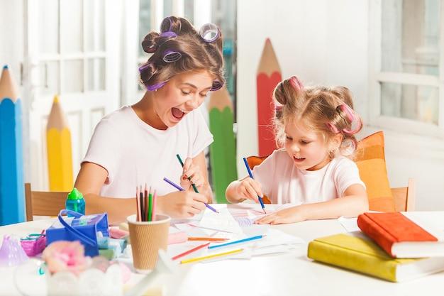 Молодая мать и ее маленькая дочь рисуют карандашами дома Бесплатные Фотографии