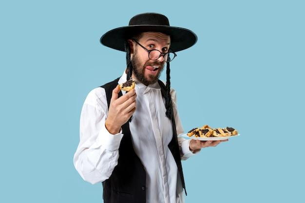 Молодой ортодоксальный еврей с печеньем hamantaschen на праздник пурим. праздник, праздник, иудаизм, выпечка, традиции, печенье, концепция религии Бесплатные Фотографии