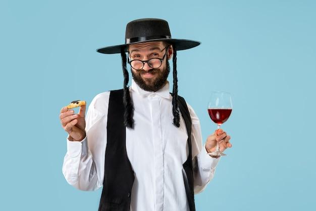 Молодой ортодоксальный еврей с печеньем hamantaschen на праздник пурим. Бесплатные Фотографии