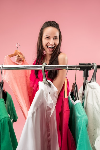 Молодая симпатичная девушка смотрит на платья и примеряет их, выбирая в магазине Бесплатные Фотографии