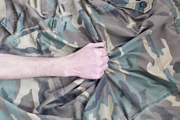 第二次世界大戦の軍服の生地を握りしめた若い兵士 Premium写真