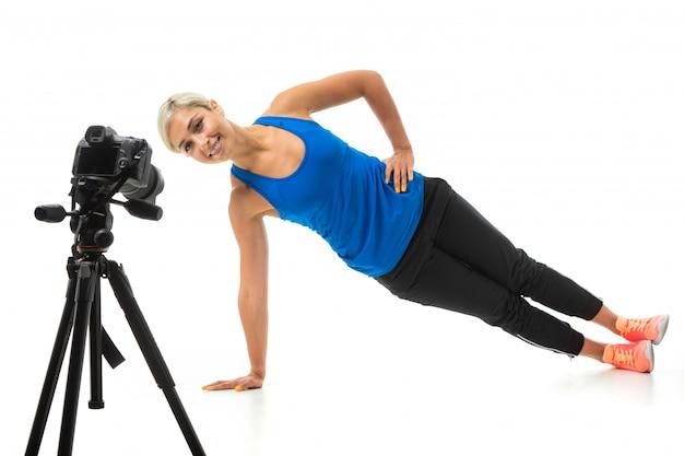 黒のスポーツトピック、黒いレギンスと明るいスニーカーで公正な髪を持つスポーティな少女は、カメラの前で演習を行います。 Premium写真