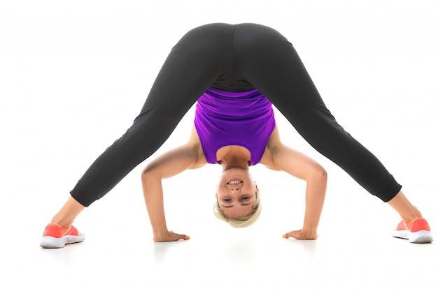 黒のスポーツトピック、黒のレギンスと明るいスニーカーで公正な髪を持つスポーティな少女は、演習を行います。 Premium写真