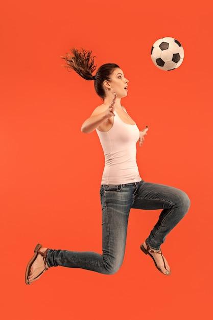 赤い背景のスタジオでジャンプしてボールを蹴るサッカーサッカー選手としての若い女性。 無料写真