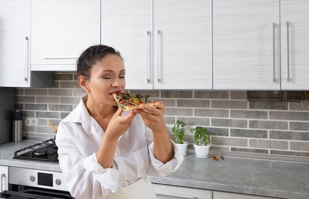 若い女性シェフはチーズなしのビーガンピザを味わい、喜んで目を閉じました。 Premium写真