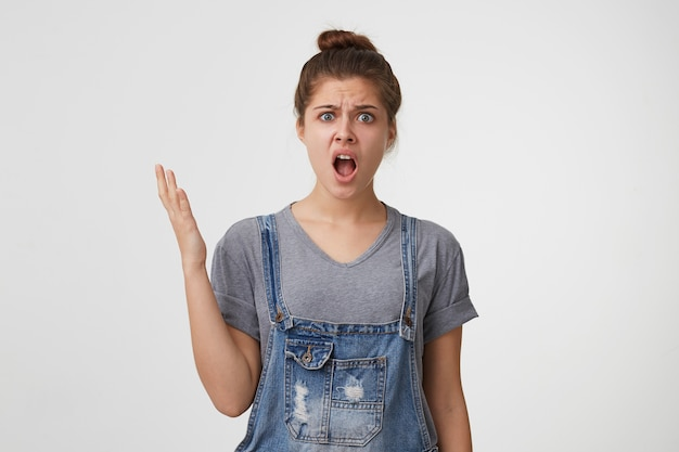 驚いた若い女性は不機嫌で、これがどのように起こったのか理解できません 無料写真