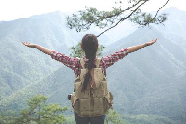 Молодая женщина протянула обе руки к вершине холма в тропическом лесу вместе с рюкзаками в лесу. приключения, пеший туризм. Бесплатные Фотографии