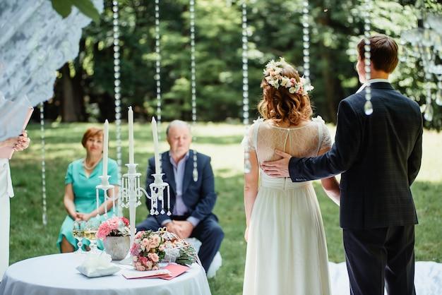 結婚式のカップルは屋外の結婚式でthei両親の隣に立っています。 Premium写真