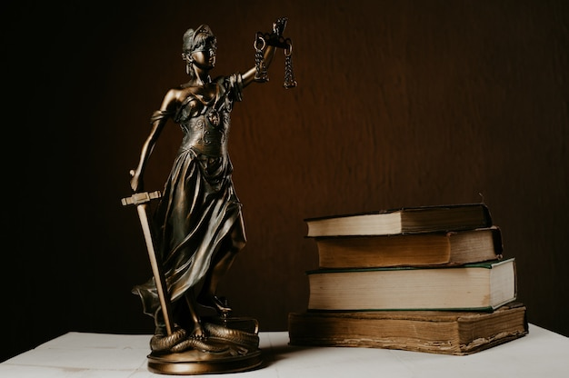 Themis figurine stands on a white wooden table next to a stack of old books. Premium Photo