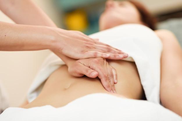 Therapist applying pressure on belly. hands massaging woman abdomen. Premium Photo