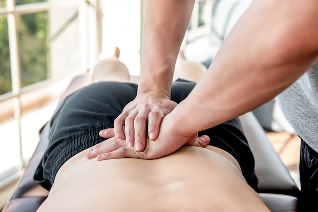Therapist giving lower back sports massage to athlete male patient Premium Photo