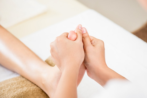 Therapist giving relaxing reflexology thai foot massage to a woman in spa Premium Photo