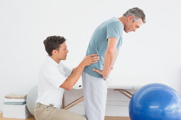 Therapist massaging mans lower back in gym hospital Premium Photo