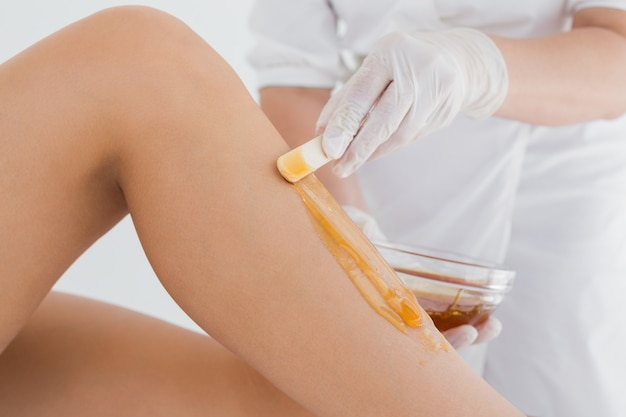 Therapist waxing womans leg at spa center Premium Photo