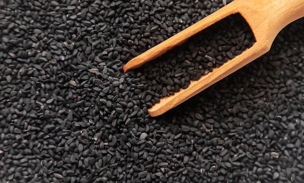 黒いクミンの種がたくさんあります。セレクティブフォーカス。自然。 Premium写真