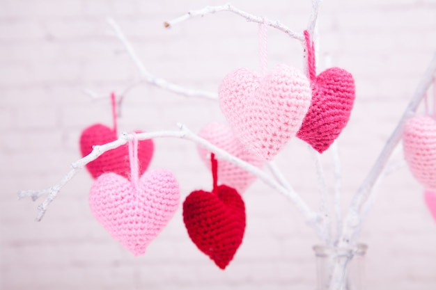 There are many pink knitted hearts on white branches. glass bottle. valentine's day. Premium Photo