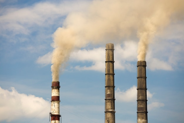 Thermal power station tall pipes with thick smoke Premium Photo