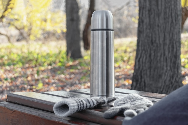 Thermos with hot tea or coffee on a bench in autumn park Premium Photo