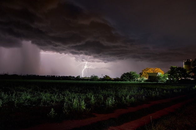 Thick clouds over the village, rain and lightning at night Premium Photo