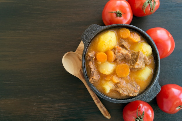 Thick hungarian soup, the goulash. on dark background. Premium Photo
