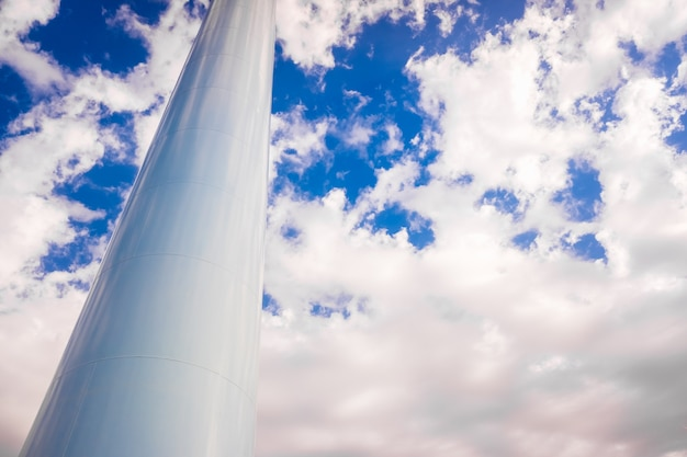 青空の背景に分離された、塔の基部として垂直位置にある太い金属製の白いパイプ。 Premium写真