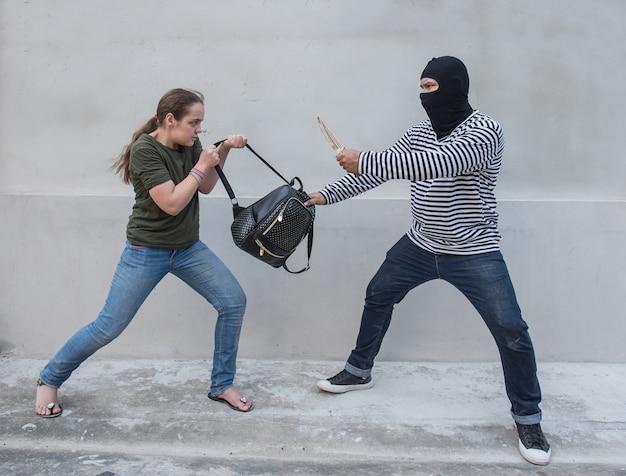 Thief holding knife pillage women,scramble bag Premium Photo