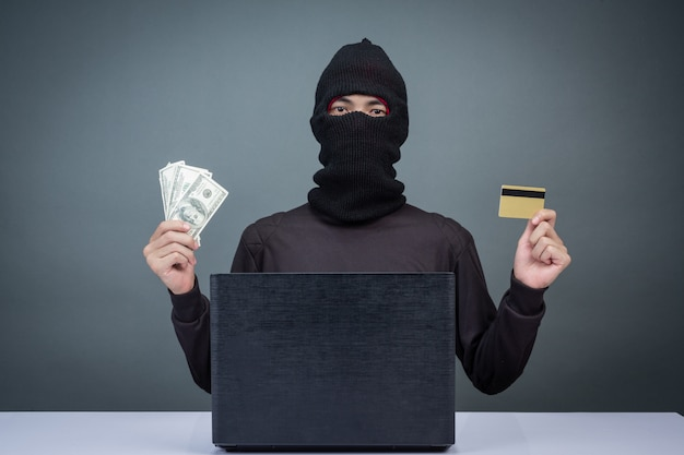 Thieves hold credit cards using a laptop computer for password hacking activities. Free Photo