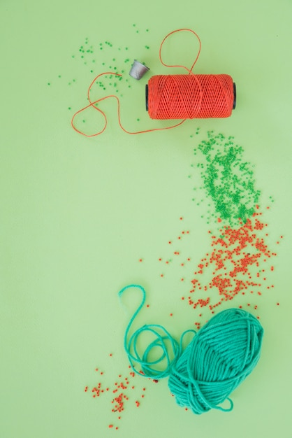 Thimble; yarn spool; red and green beads and wool on green backdrop Free Photo