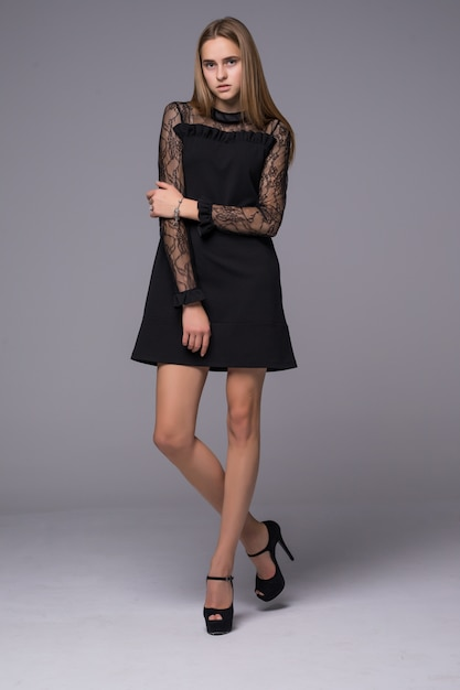 Тонкая фигура девушки одета в черное шелковое платье с кружевом Бесплатные Фотографии