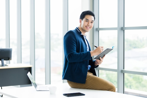 Thinking of asian young businessman working with read the note recorded in the business plan notebook and laptop computer,smartphone sit on the table in the office room . Premium Photo