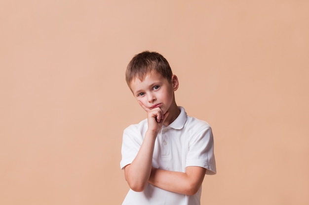 Thinking boy looking at camera standing in front of beige backdrop Free Photo